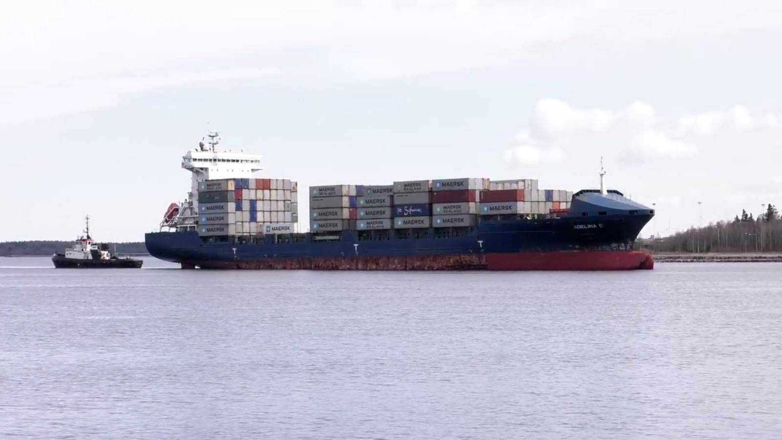 Containerfartyg till havs följt av en mindre båt.