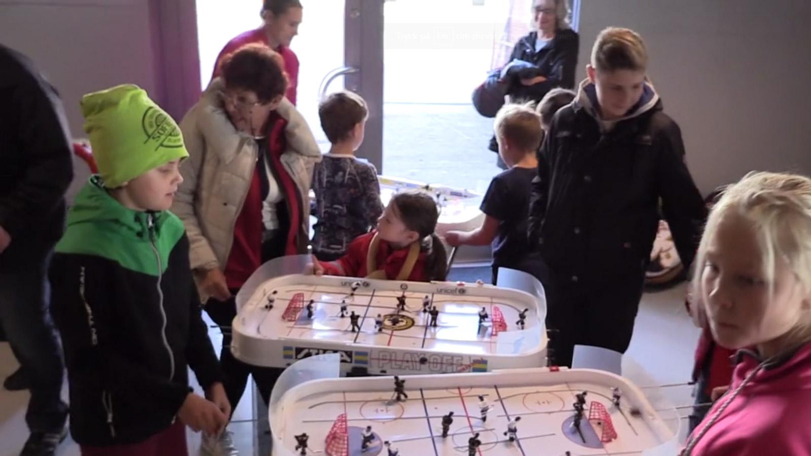 Barn och vuxna spelar bordshockeyspel.