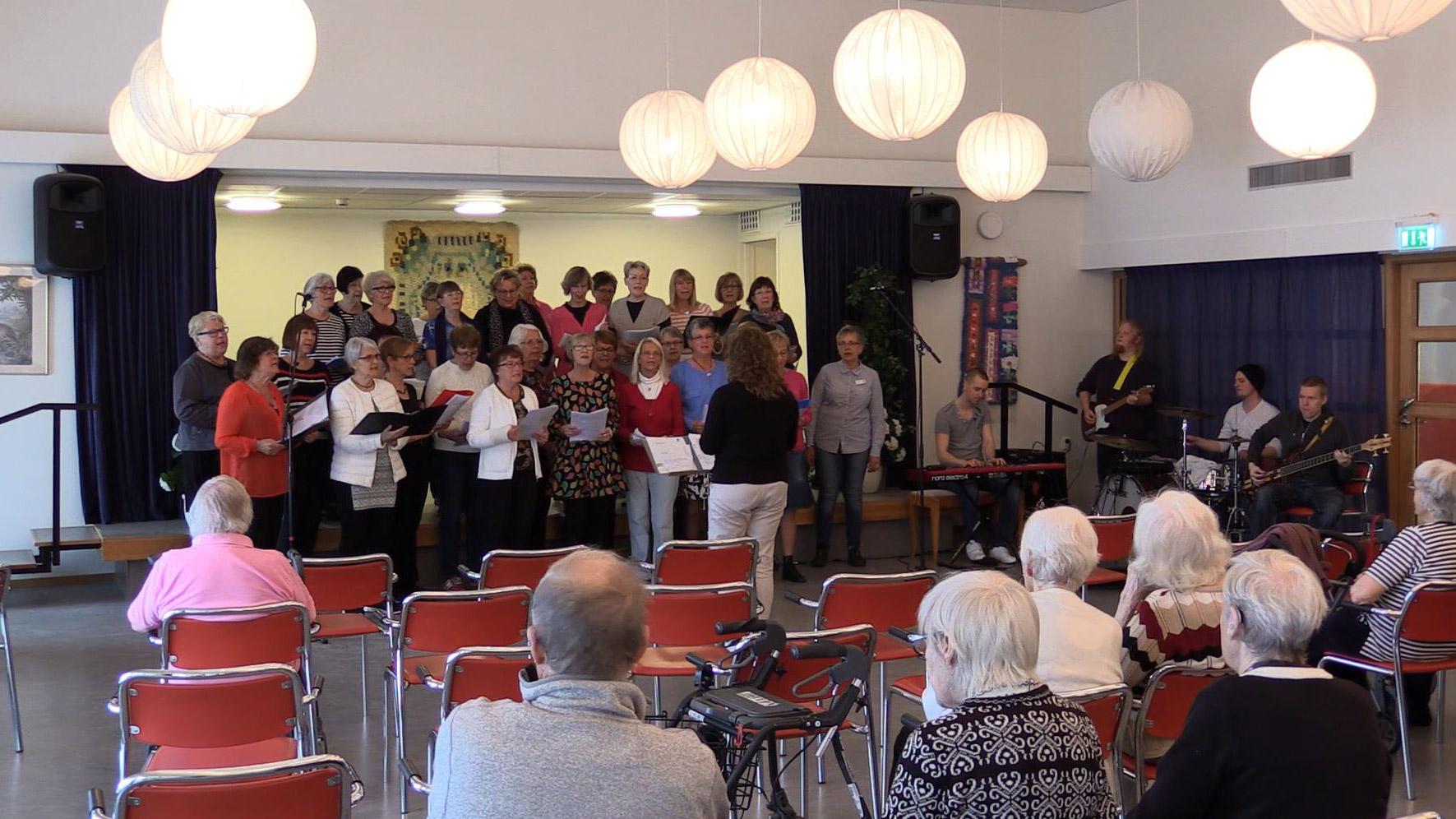 Seniorkör sjunger för publik.