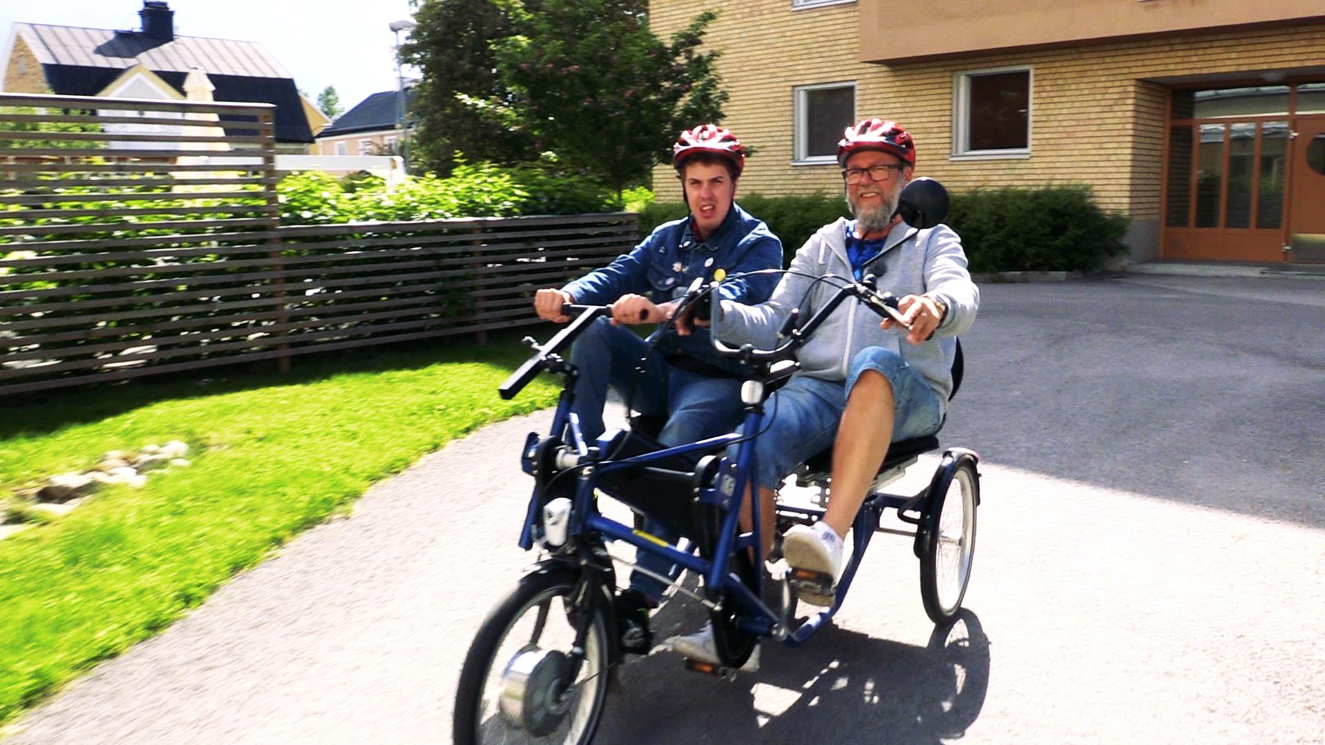Två manliga personer cyklar tillsammans i en parcykel