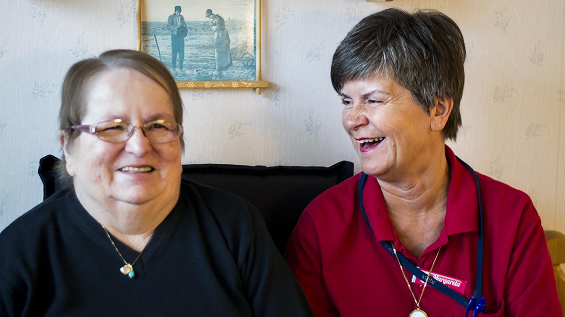 En brukare med hemtjänstpersonal som sitter bredvid varandra och skrattar