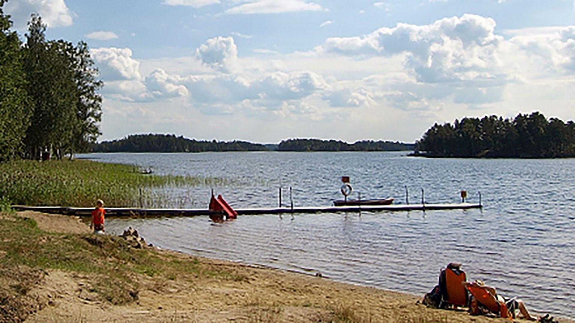 Vatten, brygga och sandstrand vid Högbacka