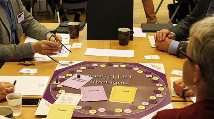 Bild på grupp som sitter och spelar brädspelet Samspelet.