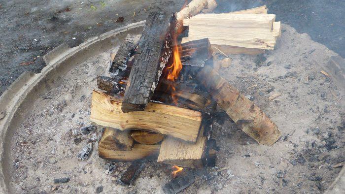 Brinnande ved på en grillplats