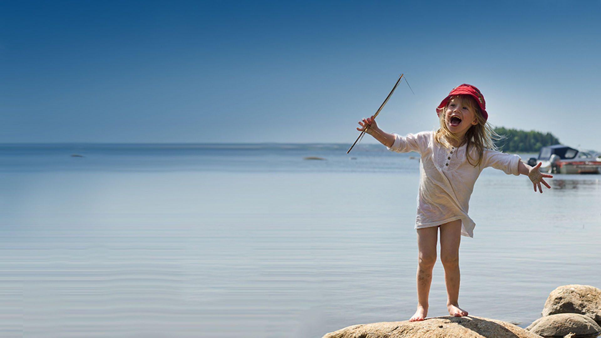 Barn står på en sten med havet i bakgrunden