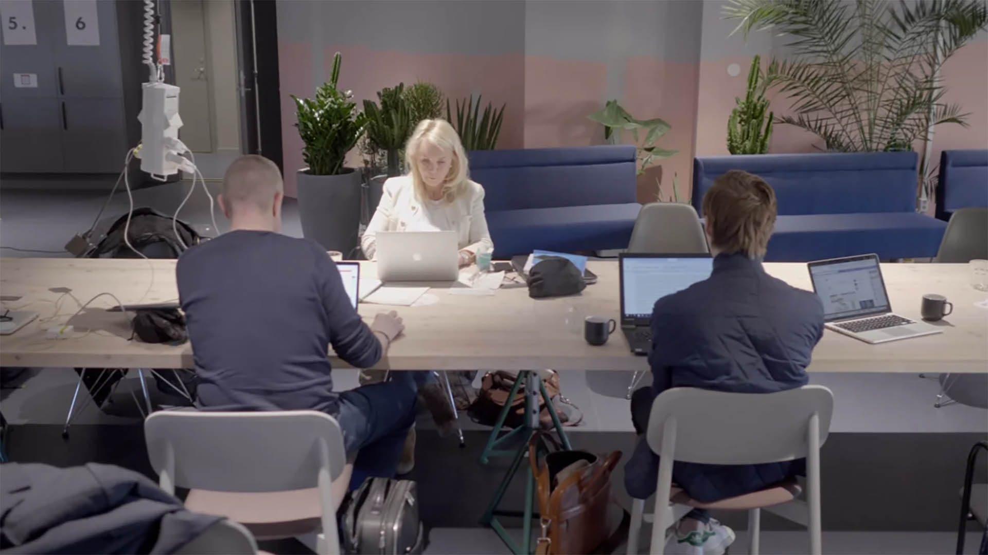 Tre personer som sitter vid ett skrivbord