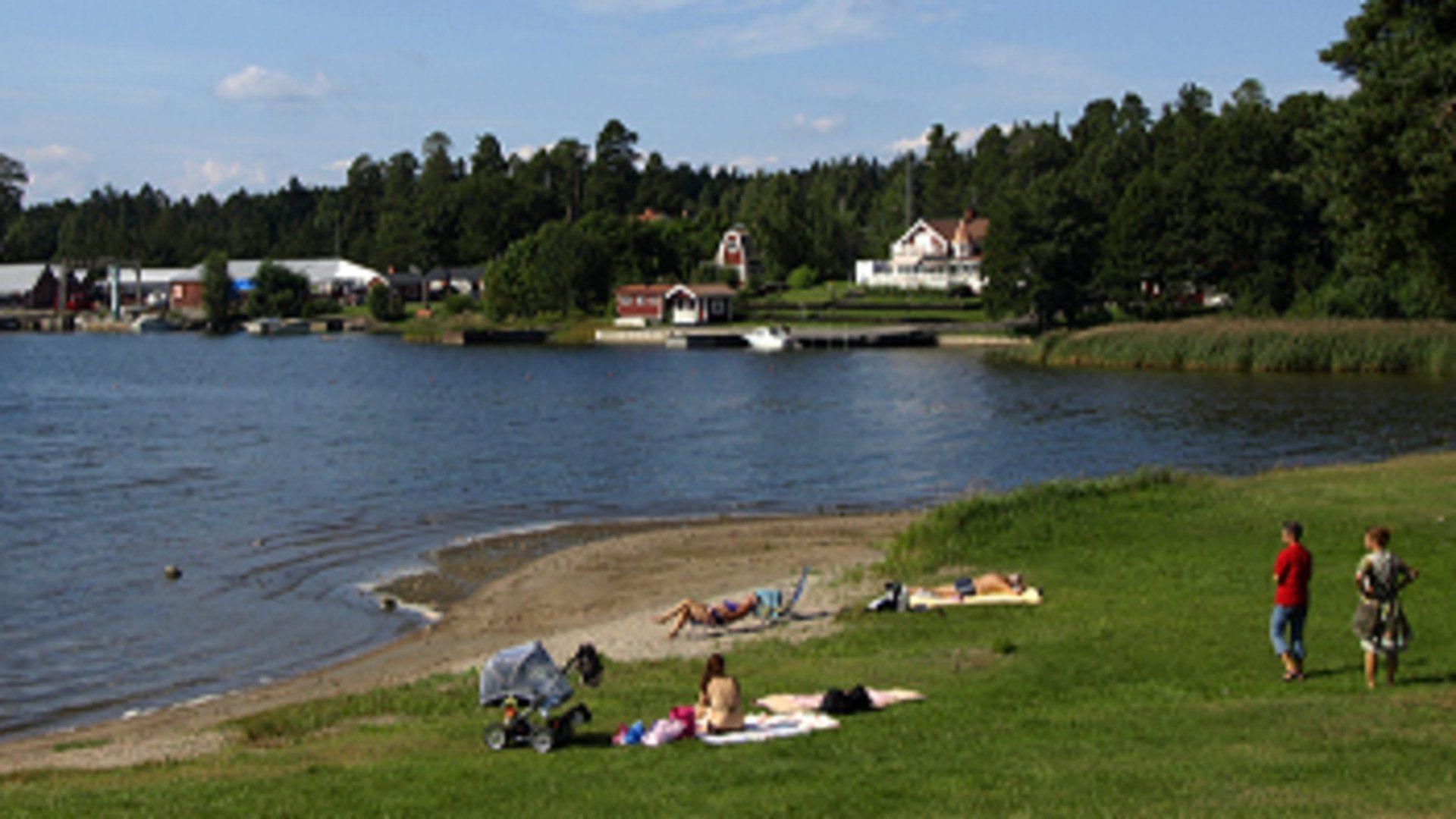 Vatten, sandstrand och gräsmatta vid Engesberg