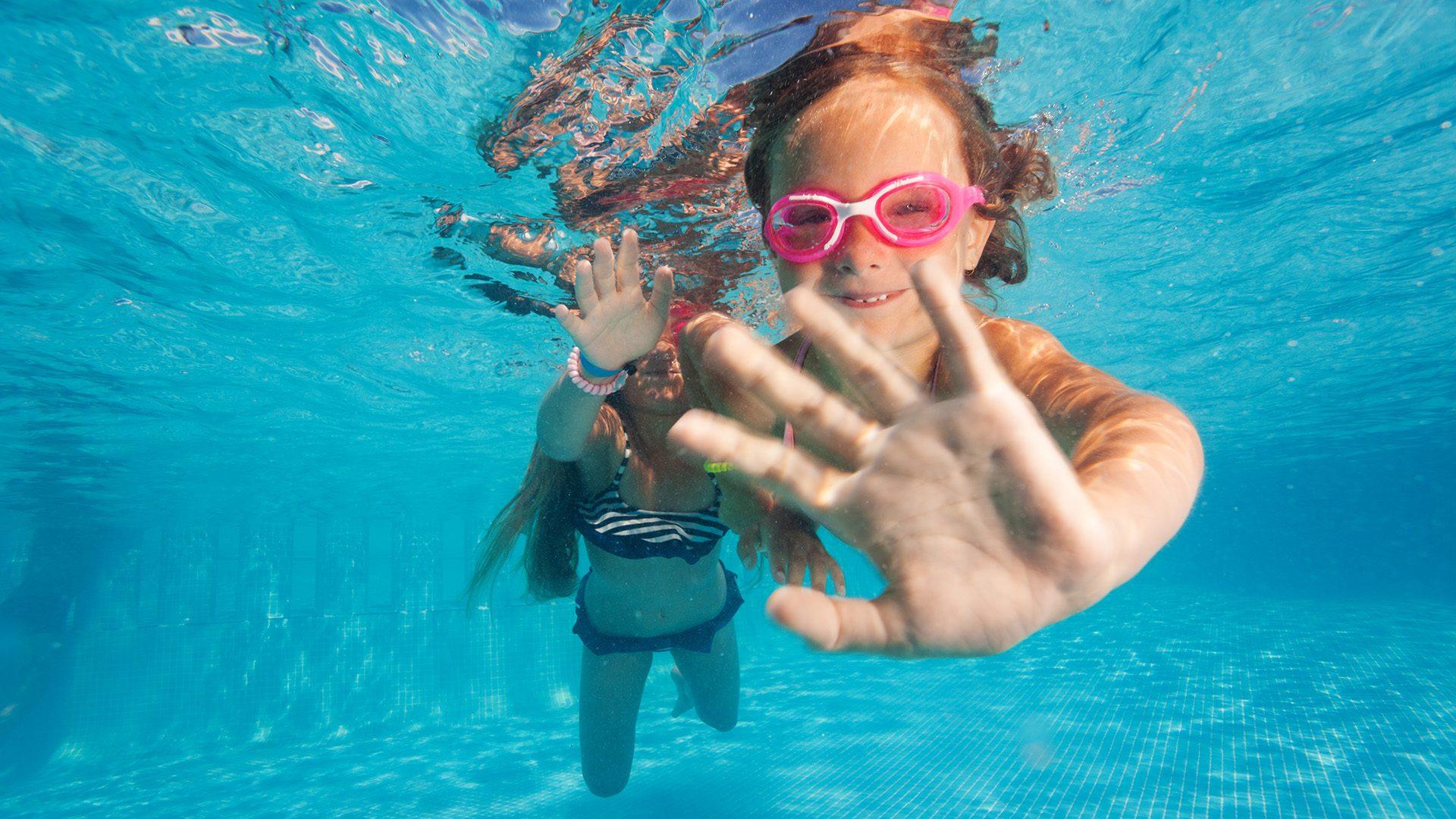 Två flickor dyker i en pool