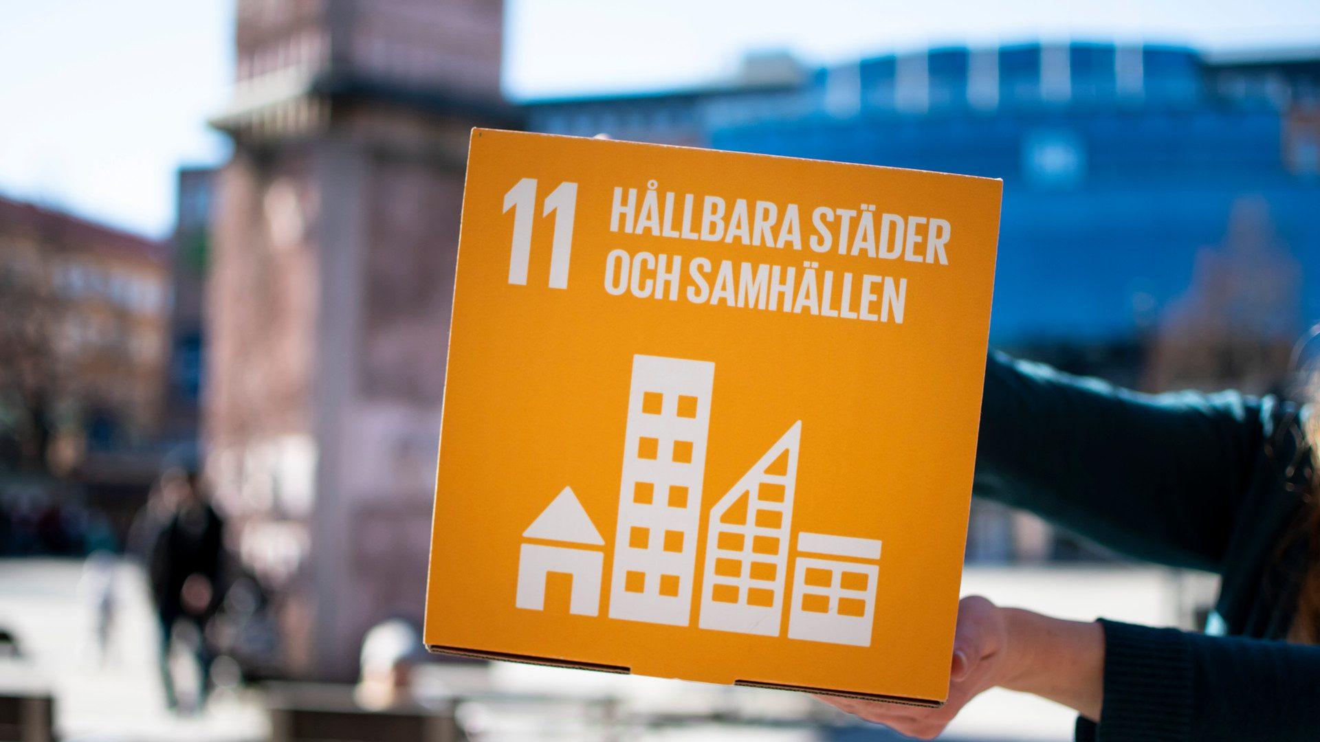 En skyld med texten Hållbara städer och samhällen hålls upp på Stortorget i Gävle.