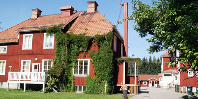 Röd skola med klätterväxter på fasaden.