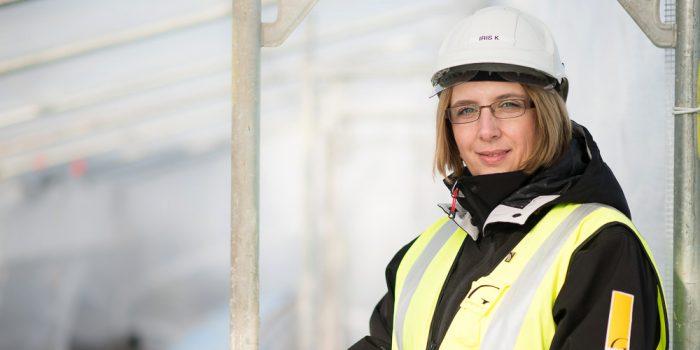 Kvinna i hjälm står vid ett bygge.