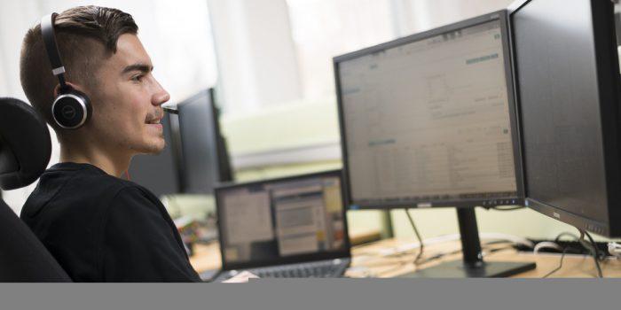 Man från IT-avdelningens support sitter vid en dator.