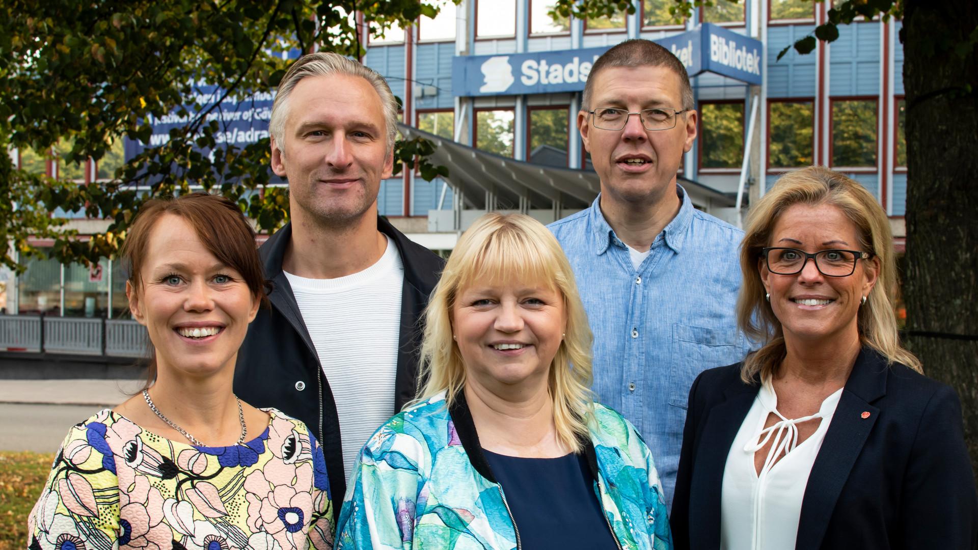 Fem politiker från majoriteten i kommunfullmäktige står framför stadsbiblioteket i Gävle