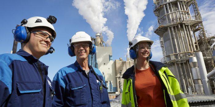Tre personer med hjälm och hörselkåpor framför en fabrik.