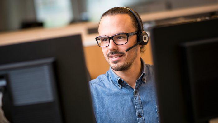 Man pratar i telefon med headset och sitter framför två datorskärmar.