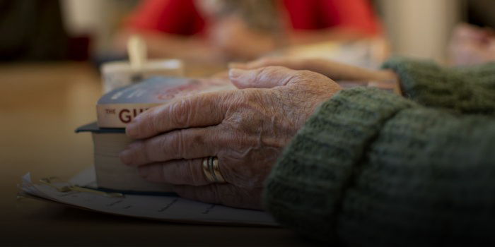 Äldre händer håller i en bok