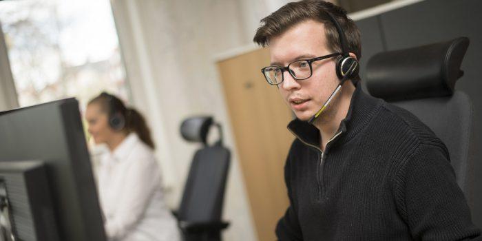 En man med headset framför en dator.