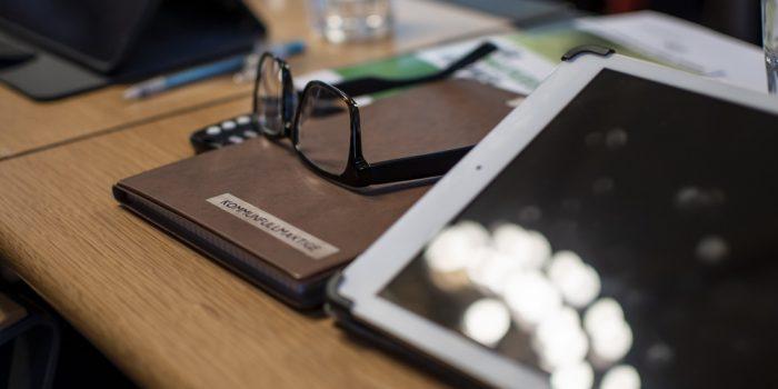 Ett skrivbord där det finns glasögon, kalender och en Ipad.