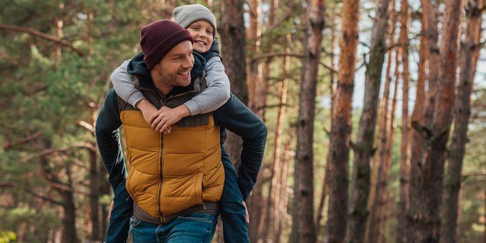 Ung man bär ett skrattande barn på ryggen