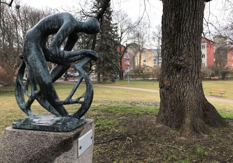 Skulptur av en människa som böjer sig över ett föremål. I bakgrunden syns träd, blommor och en öppen gräsyta.