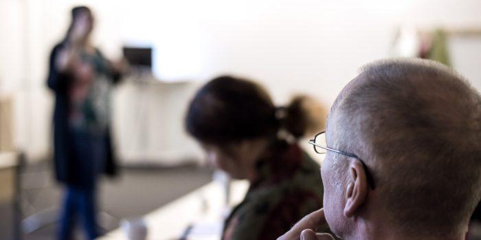 En grupp människor som lyssnar på en föreläsare.