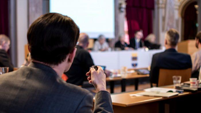 Politiker röstar i kommunfullmäktige.