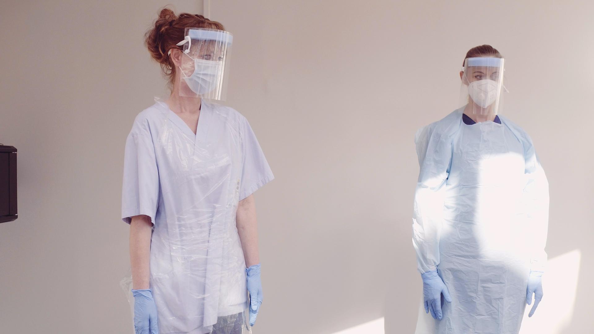 Två vårdpersonal står med skyddsvisir, munskydd och handskar.