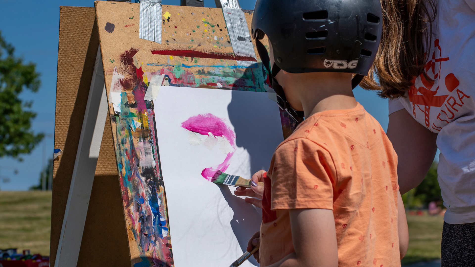 Barn med hjälm målar tavla utomhus