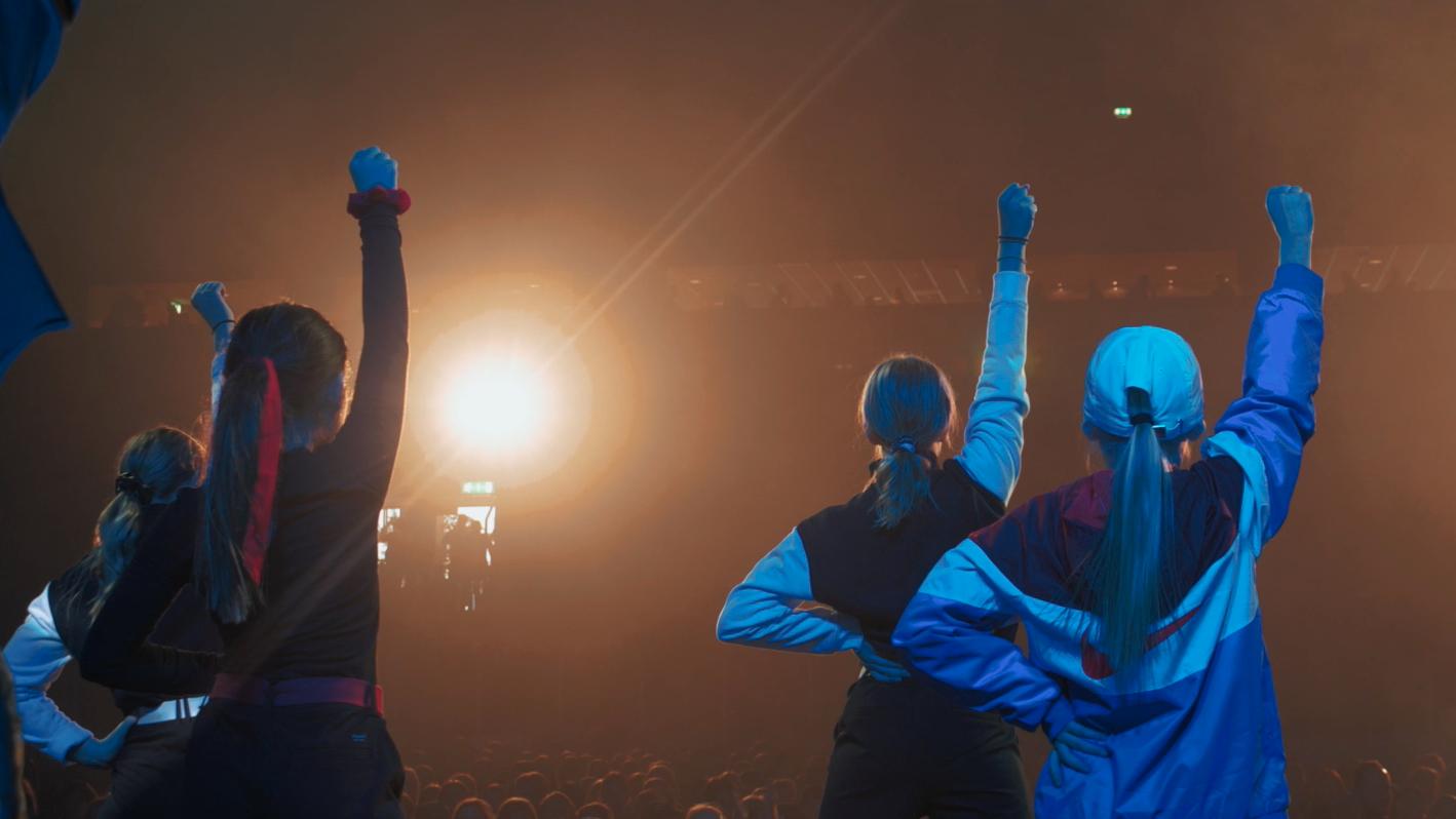 Fyra tjejer står i rampljuset på en scen och sträcker upp sina knutna högernävar i luften.