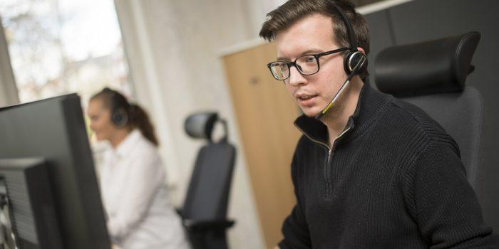 Medarbetare kundtjänst med sitter headset framför en dator.