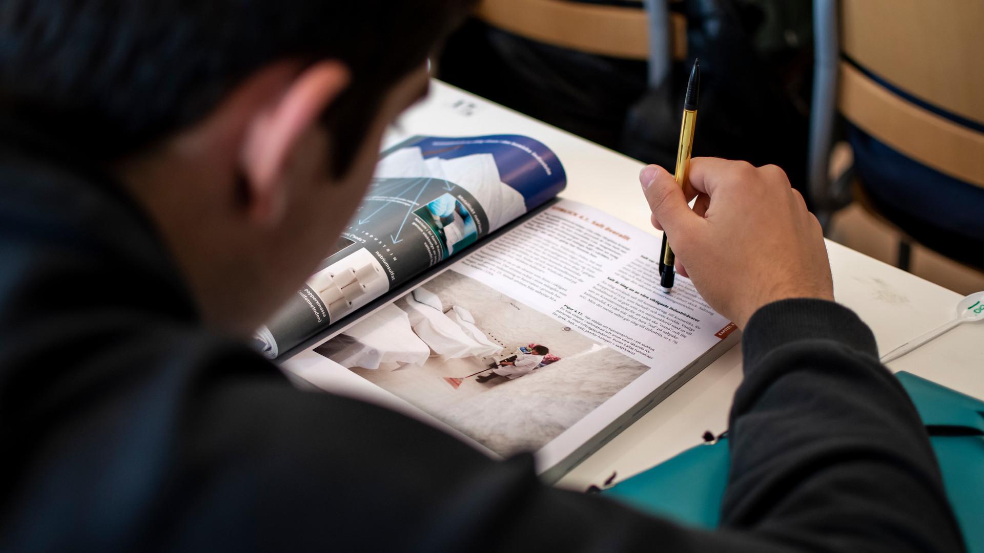 Elev som läser en bok i ett klassrum