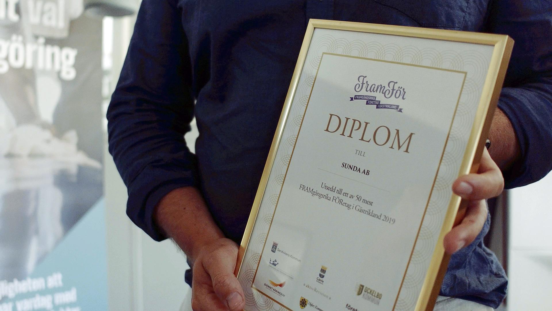 Person håller upp ett diplom från FramFör.