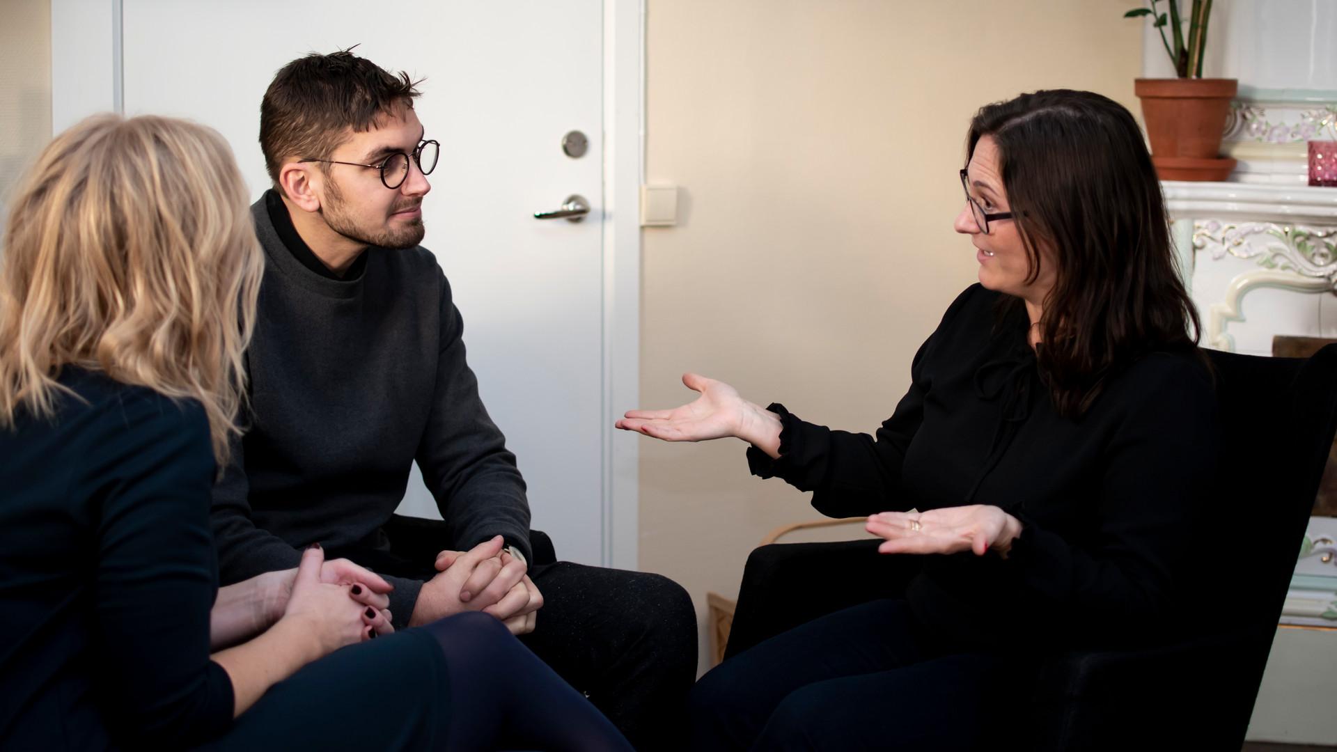 Tre personer sitter ner och pratar med varandra