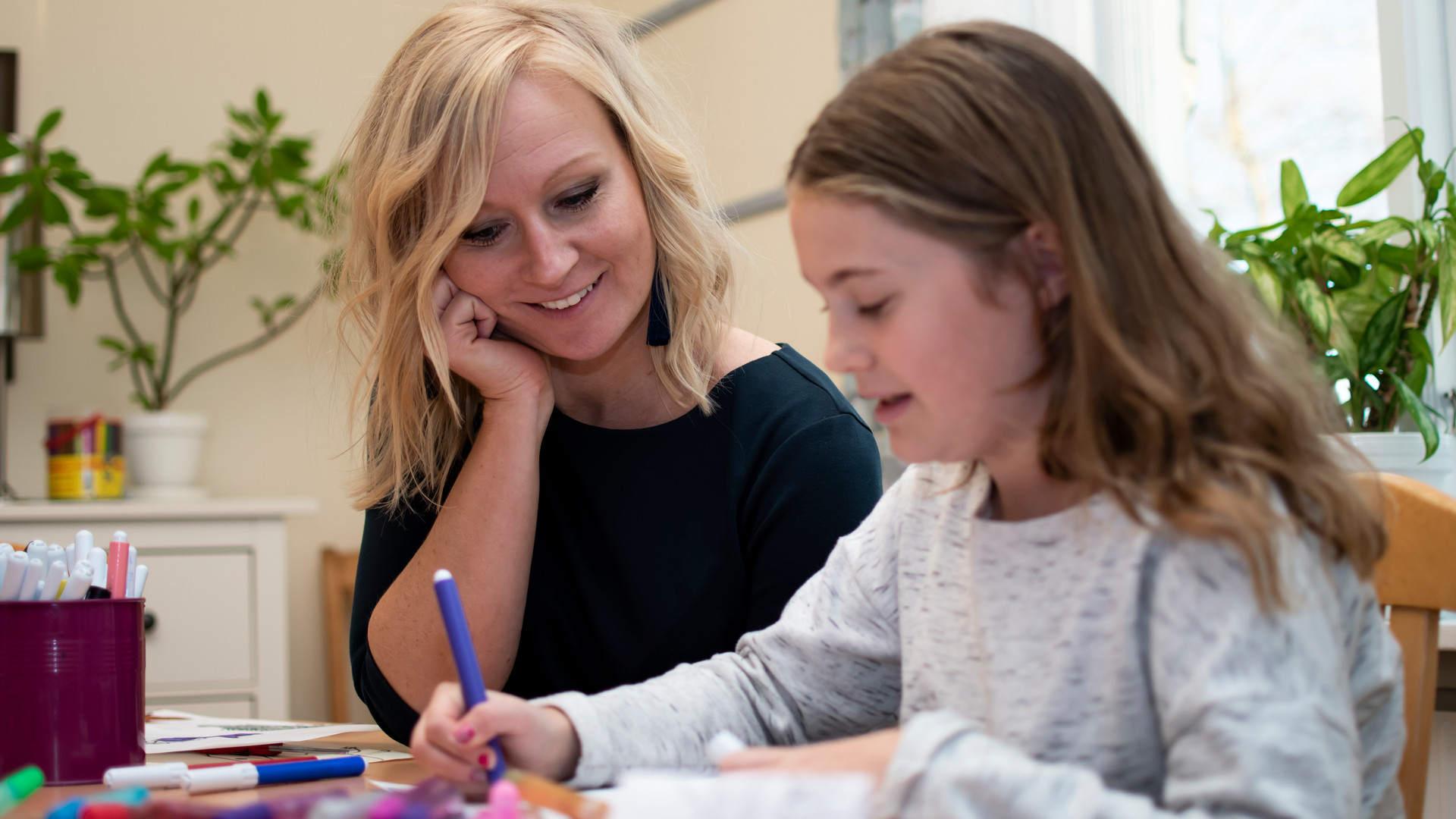 Barn målar tillsammans med en fritidspedagog