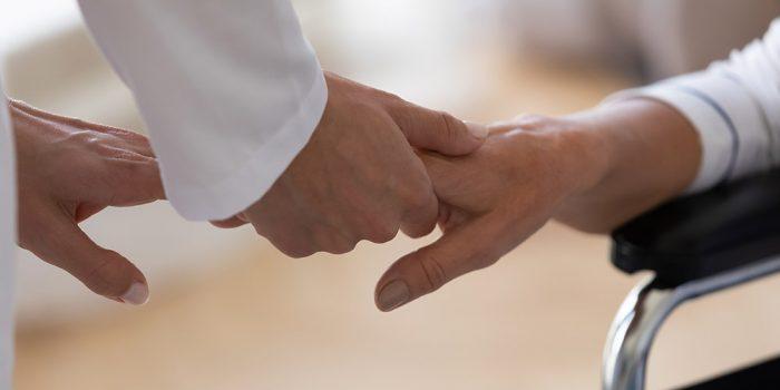 Två personer håller varandras händer.