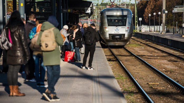 Tåg närmar sig perrong med väntande människor.