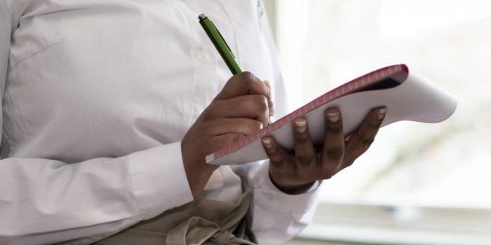 En kvinna håller i en penna och block