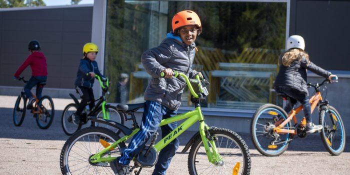 Fyra barn som cyklar på en grusplan