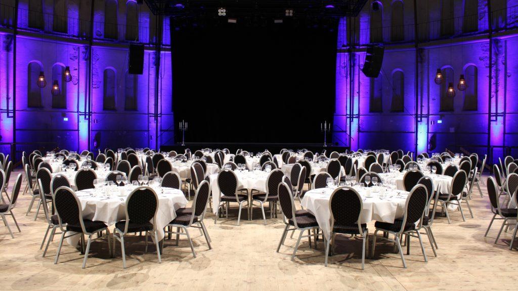 Många runda bord men fin dukning framför scen med blått belysning i Stora Gasklockan