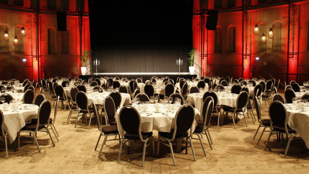 Många runda bord men fin dukning framför scen med röd belysning i Stora Gasklockan