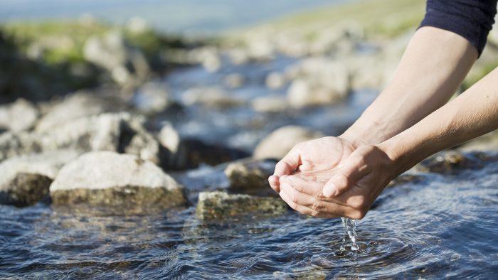 Kupade händer lyfter vatten ur en bäck.