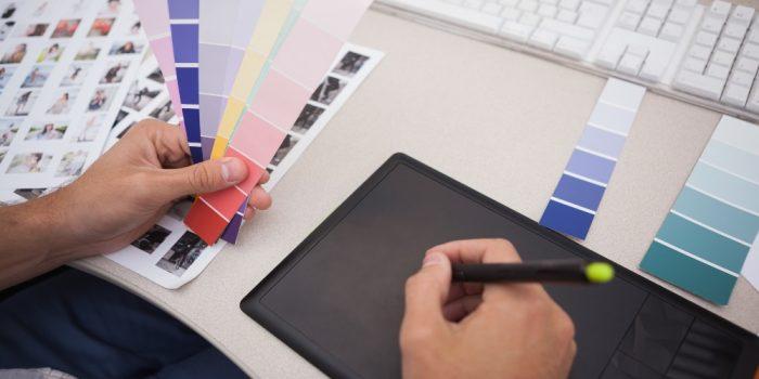 Grafisk designer som ritar på en ritplatta och håller i färgkartor.