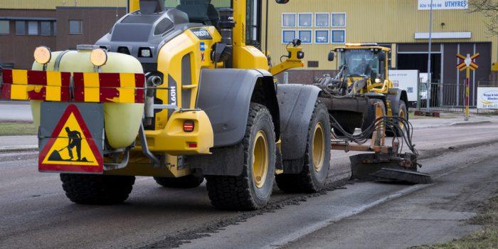 Två maskiner utför vägarbeten.