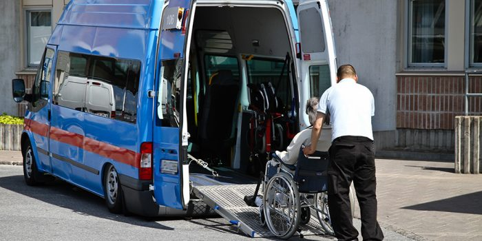 Kvinna i rullstol får hjälp med att resa.