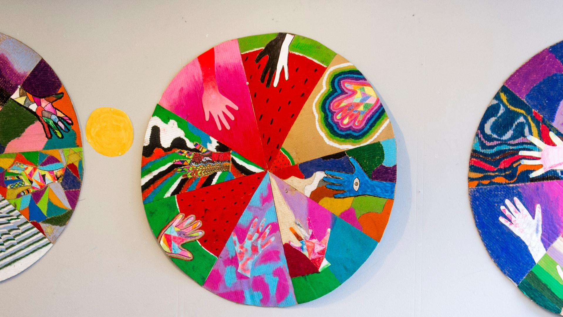 Konstverk bestående av rund skiva med händer i olika färger.