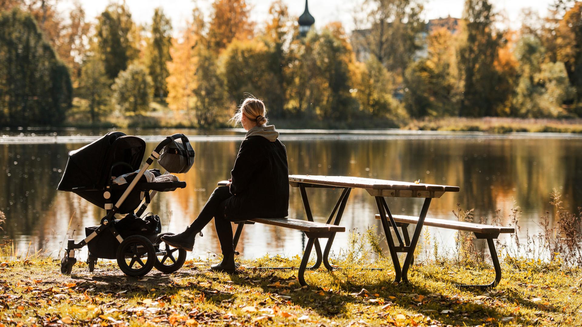 Kvinna med barnvagn som sitter på en parkbänk vid ån.