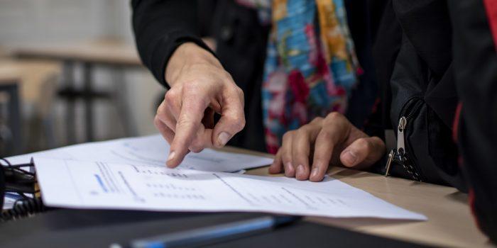 Ett finger som pekar på ett dokument.