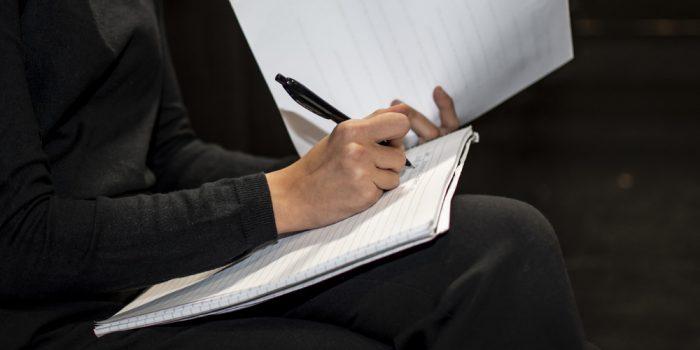 Hand som skriver i ett kollegieblock.