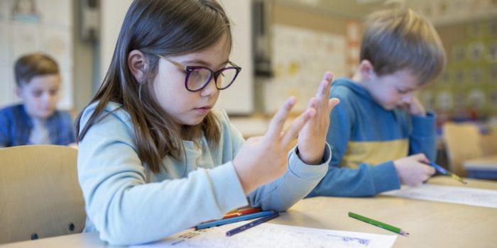 En liten flicka som räknar på fingrarna.
