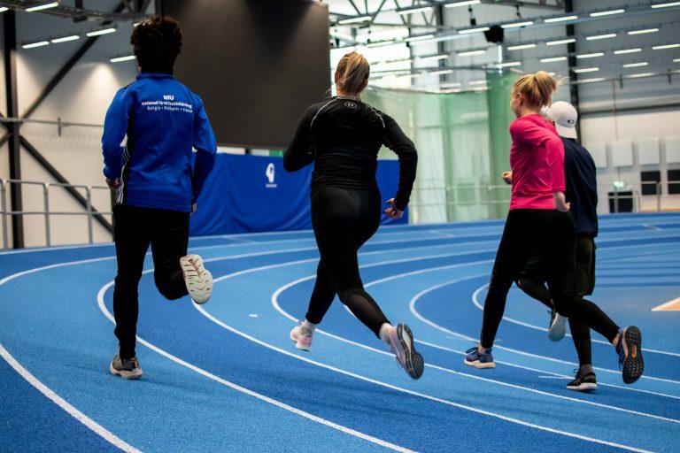 Elever springer på inomhuslöparbana